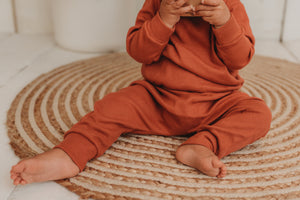 detailed shot of baby girl toddler wearing handamde lounge set in orange rust comfy cosy winter clothing sustainable unisex ribbed fabric