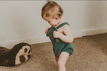 Load image into Gallery viewer, girl walking into a room wearing the forest green bohemian handmade summer romper with adjustable straps easy to layer up hippy sustainable baby toddler clothing