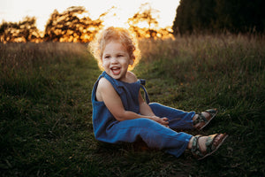 toddler boy sat in a meadow sunset behind wearing handmade bohemian romper with adjustable straps in blue curly hair hippy style clothing unisex eco friendly sustainable