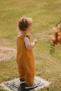 toddler boy stands in a field in orange bohemian romper adjustable straps unisex hippy clothing baby girl curly hair sustainable handmade