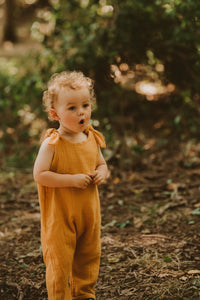 toddler boy stands in forest in orange bohemian romper adjustable straps unisex hippy clothing baby girl curly hair sustainable handmade