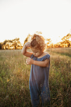 Load image into Gallery viewer, toddler boy stood in a meadow sunset behind wearing handmade bohemian romper with adjustable straps in blue curly hair hippy style clothing unisex eco friendly sustainable