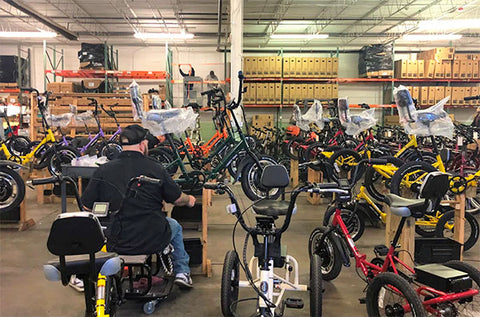 A worker assembles battery powered bicycles and tricycles