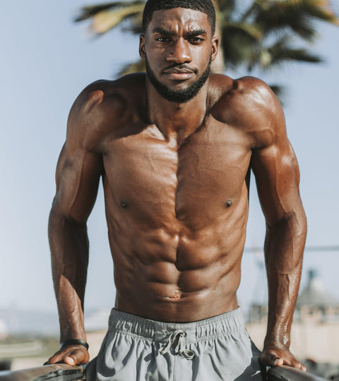 Topless muscular black man doing dip exercises