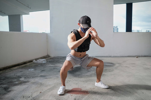 Squat with weighted vest grav male with cap