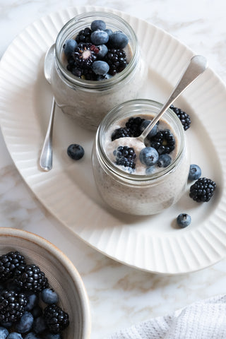 Two jars filled with vegan chia pudding and berries