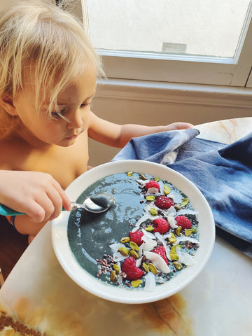 Child sitting at table enjoying a blueberry yogurt bowl with blue linen