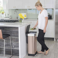 45L rectangular pedal bin with liner pocket - rose gold finish - lifestyle woman throwing stems away