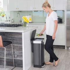 45L rectangular pedal bin with liner pocket - black finish - lifestyle woman throwing stems away