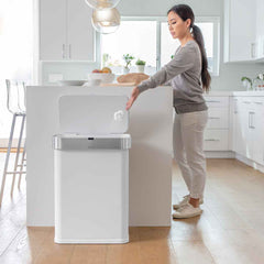 58L rectangular sensor bin with voice and motion control - white steel - lifestyle woman throwing rubbish away