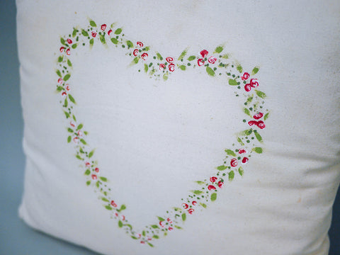 Dotty rose heart wreath painted on to a white fabric cushion cover