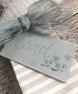 Handpainted grey gift tag decorated with folk art angels and hand lettering