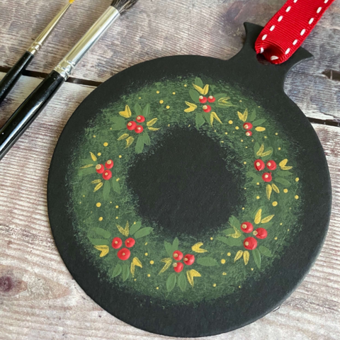 Two handpainted bauble shapes against a wooden background. The bauble is painted with a green and gold berry wreath from You Can Folk It's painting masterclass