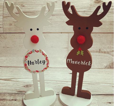 Two freestanding wooden reindeer hand painted and decorated for Christmas