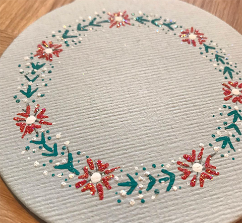 Bauble mount board shape decorated with the Poinsettia design from You Can Folk It's bauble painting kit