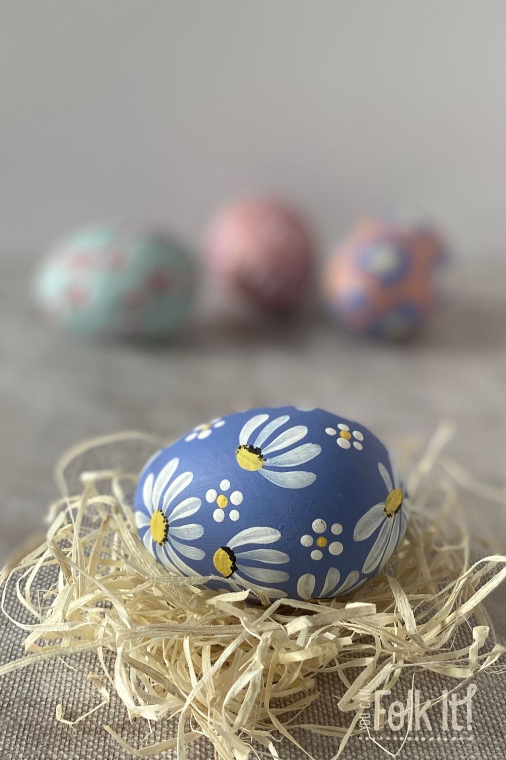 Ceramic easter egg painted in blue and hand painted with daisies from You Can Folk It's painting masterclass for beginner painters