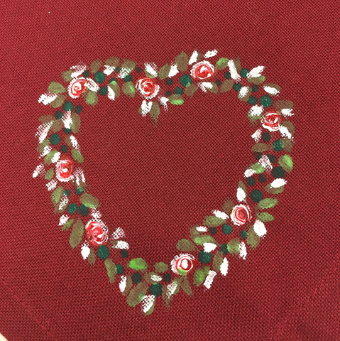 Close up of red cotton napkin containing a painted heart made up of dots of green, leaves in green and white and roses
