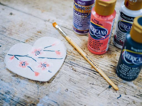 Image of a fabric heart painted with an oriental blossom design next to a flat brush and the bottles of DecoArt Americana acrylic paints and Fabric medium.