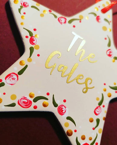 Ceramic star hanging decoration personalised with vinyl lettering and dotty designs