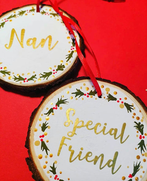 Wood slices hand painted in white and then decorated with holly and vinyl lettering