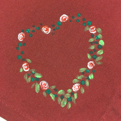 Close up of red cotton napkin containing half of a painted heart made up of dots of green, leaves and roses