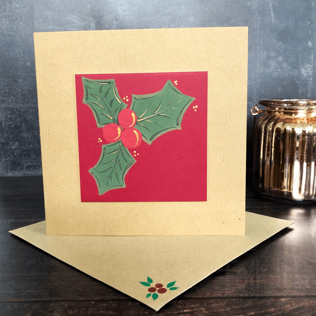 Square kraft card and envelope featuring a red square mountboard. The square is decorated with a handpainted sprig of holly across the top left corner. It is stood in front of a dark backdrop and gold decorative jar.