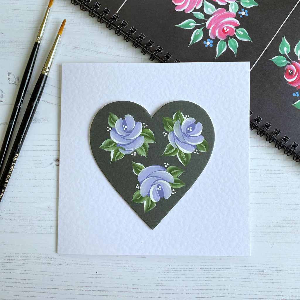 Lavender coloured folk art roses handpainted on to a charcoal heart and made into a beautiful greetings card