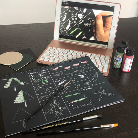 A desk covered with an iPad playing a painting tutorial from You Can Folk It. The painting booklet, brushes and paints are laid in front.