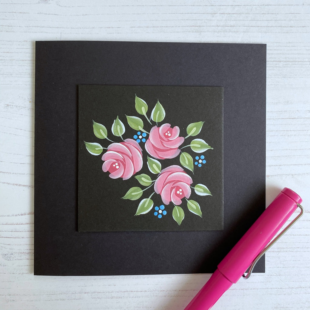 Pink folk art comma stroke roses hand painted on to a black card