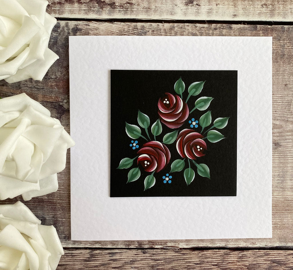 Red 'c stroke' roses painted onto a black mount board to create a beautiful Valentine's card