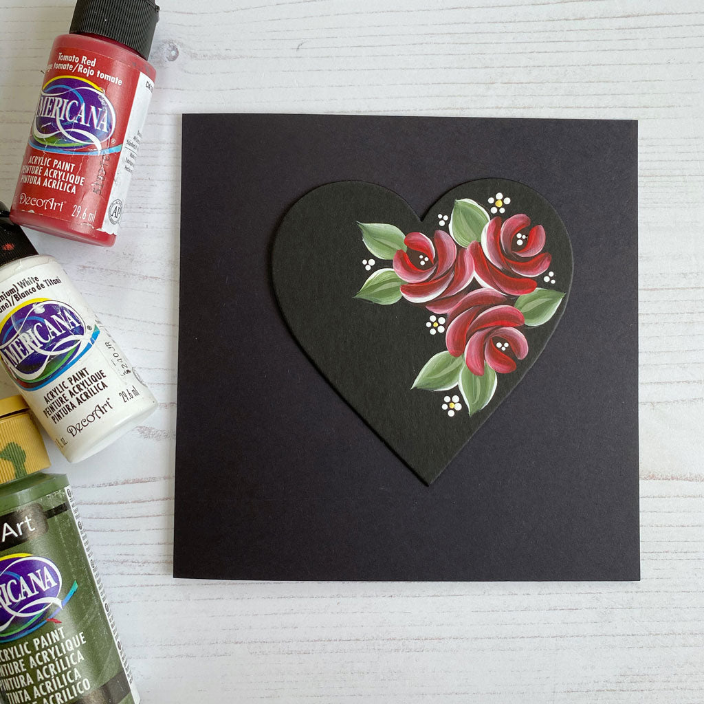 Red comma stroke roses from You Can Folk It painted onto a black card perfect for Valentine's Day