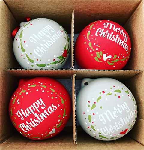 Red and white baubles decorated with wreaths and vinyl lettering