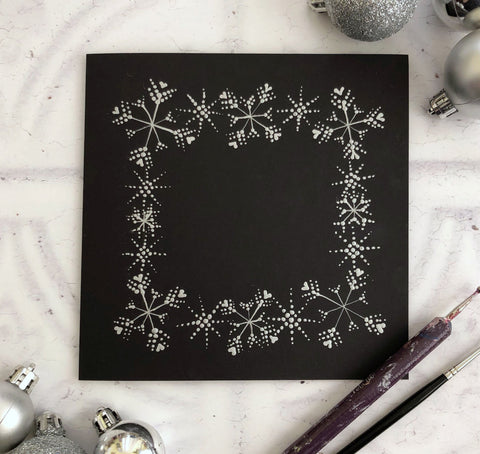Painted silver snowflakes on a black square card