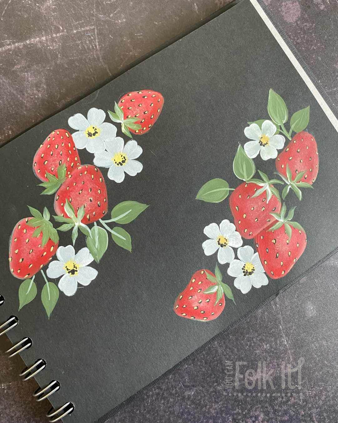 Strawberry and blossom painting on a black painting journal