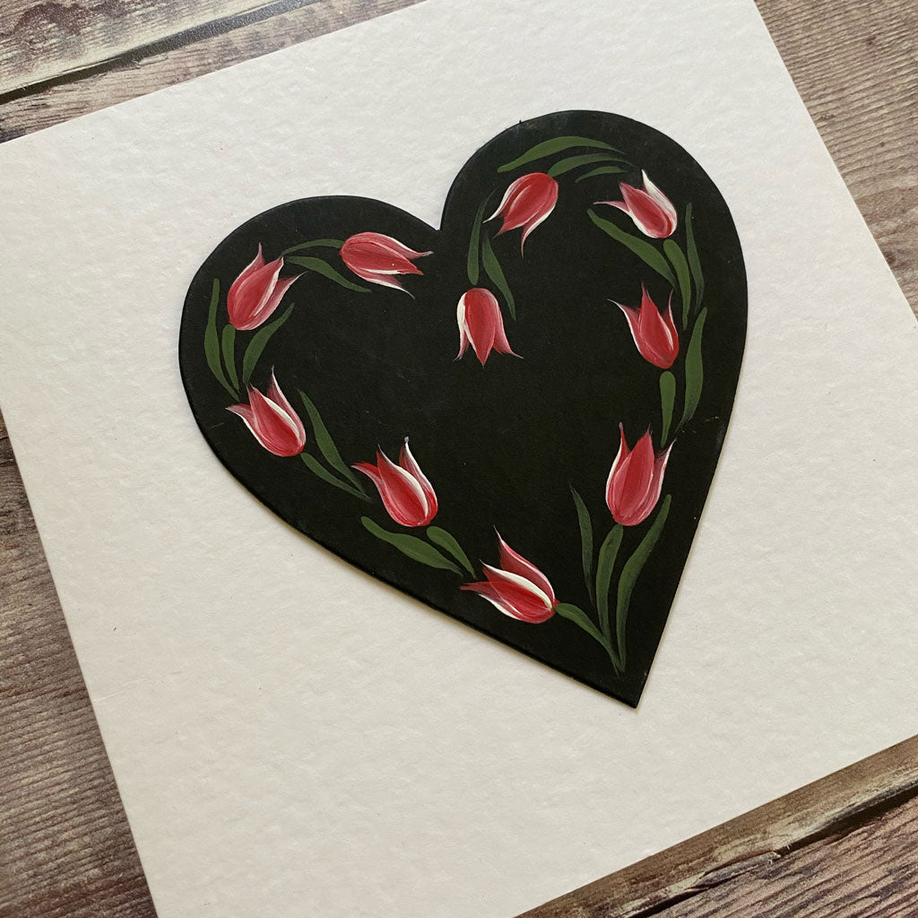 Small red tulips painted in a black heart mounted on to a hammered white card.