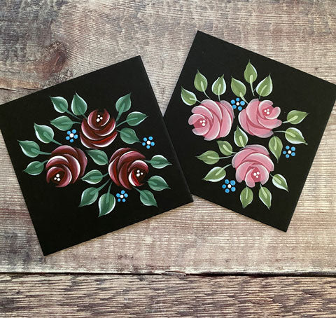 Two black squares hand painted with Folk Art roses - one red posy, one pink.