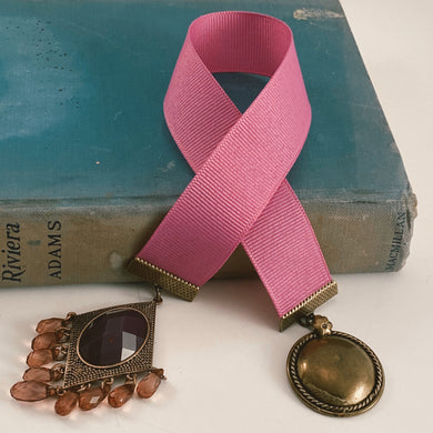 Grosgrain ribbon bookmark in bright pink palette, adorned with a large bronze-tone pendant and a pink/purple beaded accent. Size: approx. 12