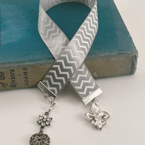 Satin ribbon bookmark in a white and gray chevron pattern, adorned with a silver-tone pendant and a silver fleur de lis charm. Size: approx. 12