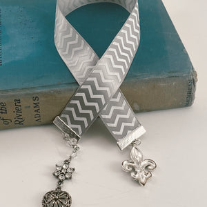 "Satin ribbon bookmark in a white and gray chevron pattern, adorned with a silver-tone pendant and a silver fleur de lis charm. Size: approx. 12"" X 1"""