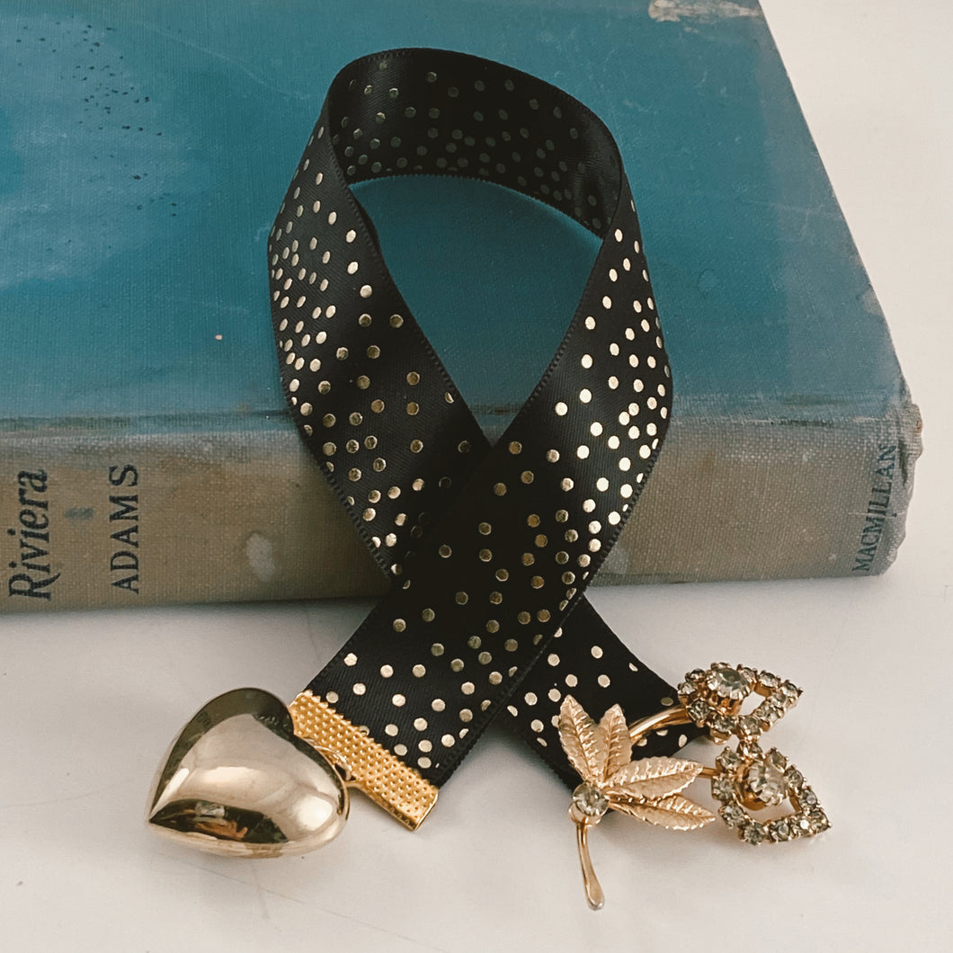Satin ribbon bookmark in black and gold palette, adorned with a gold-tone heart charm and a gold-tone vintage flower brooch. Size: approx. 12