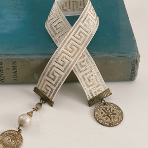 "Grosgrain ribbon bookmark in a white and gold Greek pattern, adorned with a gold coin charm and a pearl and gold medallion charm Size: approx. 12"" X 1"""