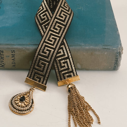 Ribbon bookmark in a black and gold palette, adorned with a gold, black and white beaded pendant and a gold chain tassel. Size: approx. 12