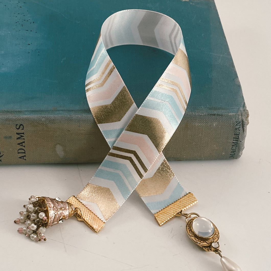 Satin ribbon bookmark in pink, blue and gold chevron, adorned with a gold-tone charm and a white beaded tassel. Size: approx. 12