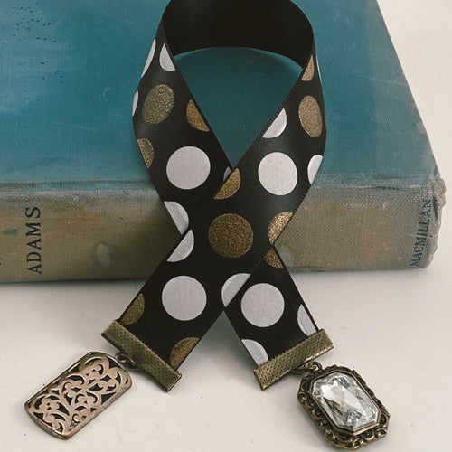 Satin ribbon bookmark in black, white and gold polka dots adorned with a gold-tone rhinestone charm and a gold-tone scrolled pendant Size: approx. 12