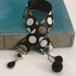 "Satin ribbon bookmark in black, white and gold polka dots, adorned with a black, beaded charm and a black rhinestone accent Size: approx. 12"" X 1"""