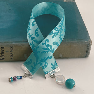 "Satin ribbon bookmark in a teal floral pattern, adorned with a teal beaded charms Size: approx. 12"" X 1"""