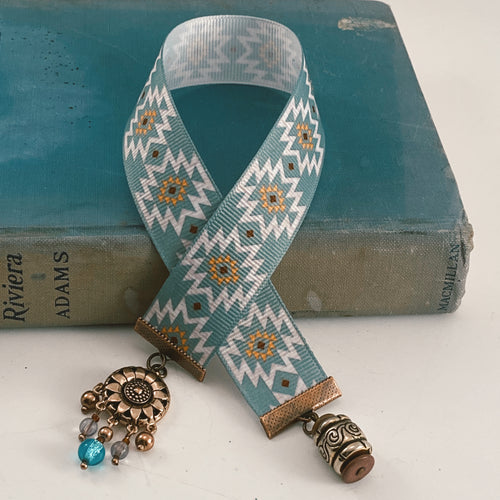 Grosgrain ribbon bookmark in turquoise and yellow Aztec pattern, adorned with a gold-tone barrel charm and a beaded flower accent Size: approx. 12