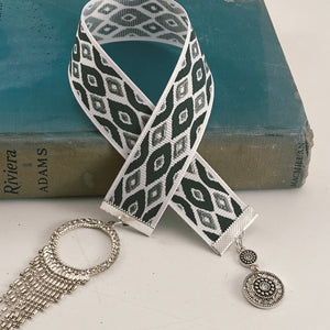 "Grosgrain ribbon bookmark in a gray, black and white pattern, adorned with a silver beaded pendant and a small silver medallion Size: approx. 12"" X 1"""