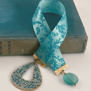 "Satin ribbon bookmark in a turquoise floral pattern, adorned with a large, gold and turquoise scrolled pendant and a blue bead accent Size: approx. 12"" X 1"""