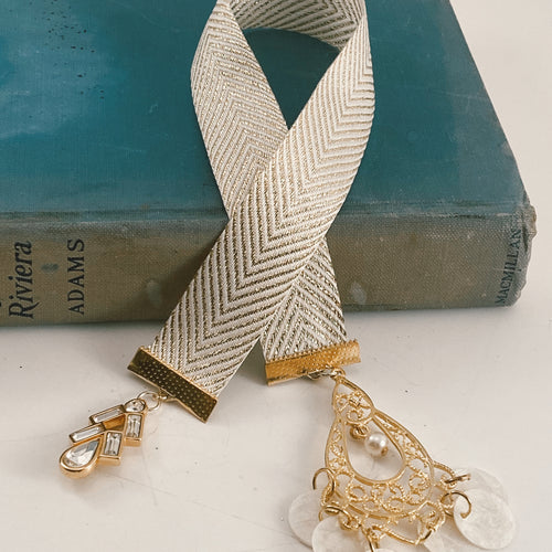 Cotton ribbon bookmark in gold and white chevron, adorned with a gold and rhinestone charm and a large, gold-tone pendant with white shell accents Size: approx. 12